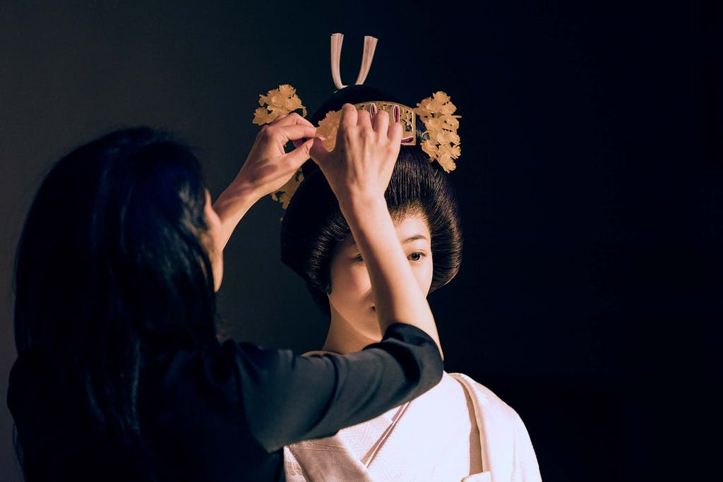 A kimono expert dresses the bride in her traditional Japanese wedding kimono.
